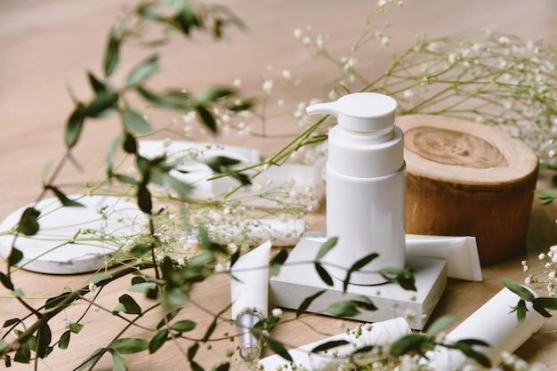 Pojemniki na butelki kosmetyczne z zielonymi liśćmi ziołowymi, pusta etykieta na oznakowanie ekologiczne, koncepcja produktów do pielęgnacji skóry naturalnej