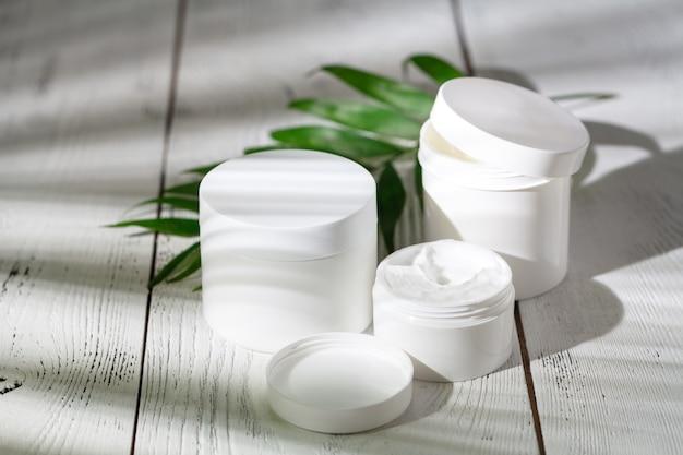 Pojemniki na butelki kosmetyczne z zielonymi liśćmi ziołowymi, puste opakowanie na makietę marki, koncepcja naturalnego ekologicznego produktu kosmetycznego