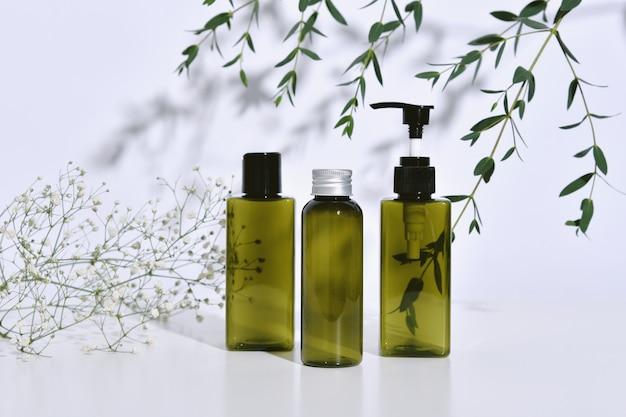 Pojemniki na butelki kosmetyczne z zielonymi liśćmi ziołowymi w cieniu i świetle, pusta etykieta ekologicznego brandingu, naturalny produkt do pielęgnacji skóry.