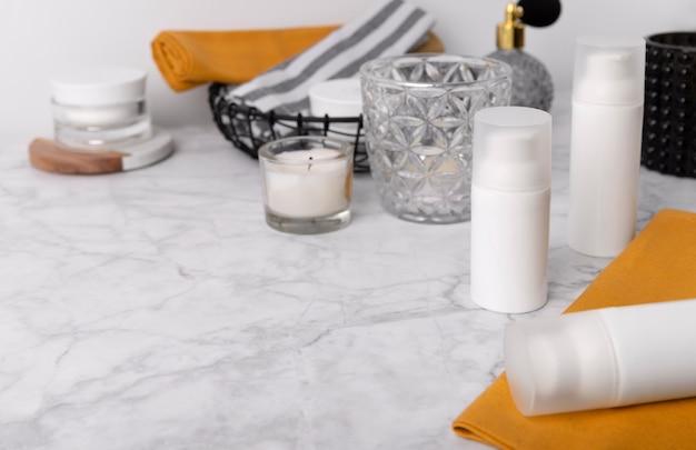 Pojemniki na butelki kosmetyczne z żółtymi ręcznikami i akcesoriami na marmurowym stole