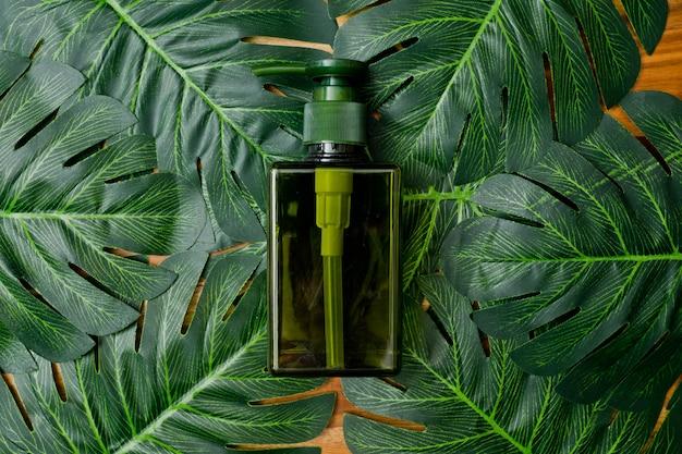 Pojemniki na naturalne kosmetyki na zielonym tle liści, pusta butelka, naturalny produkt do pielęgnacji skóry,