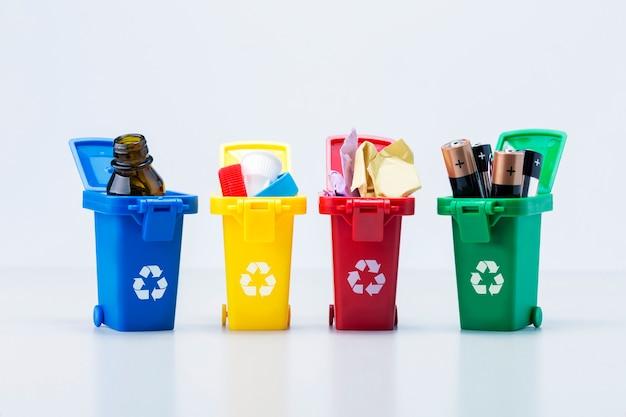 Pojemniki na śmieci z różnymi rodzajami śmieci na białym tle