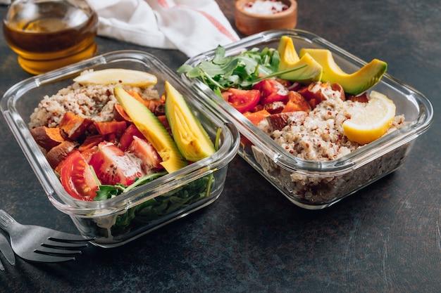Pojemniki na zdrowe posiłki wegetariańskie. surowe warzywa i komosa ryżowa na obiad na ciemnym stole.