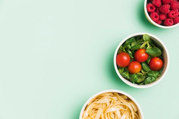 Pojemniki na żywność leżące na płasko z malinami, sałatką i makaronem z miejscem na kopię