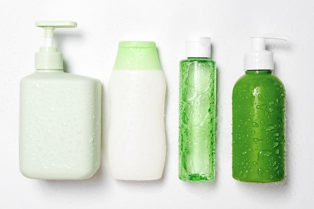 Pojemniki o różnych rozmiarach i kształtach do tonizujących odżywek, mydła i szamponu na białym tle z kroplami wody. naturalne organiczne produkty kosmetyczne