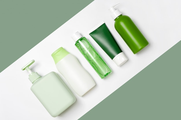 Pojemniki o różnych rozmiarach i kształtach na tonik do demakijażu, mydło i szampon na białym i zielonym tle. naturalne organiczne produkty kosmetyczne
