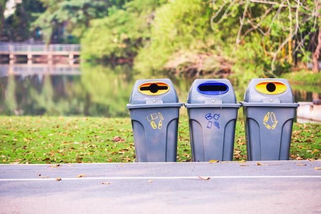 Pojemniki w parku do oddzielenia odpadów.