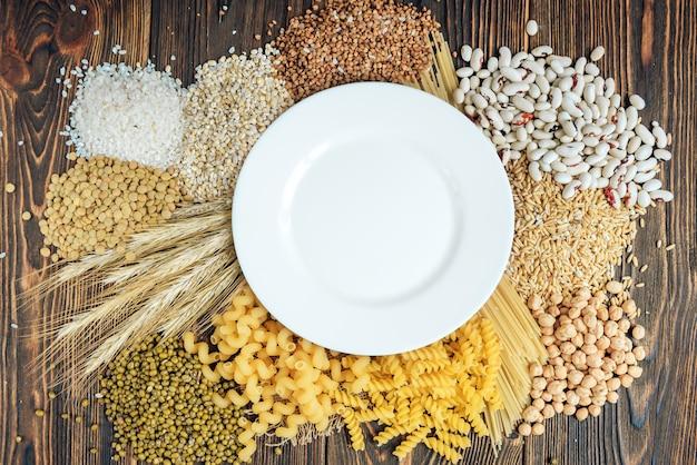 Pokarmy bogate w węglowodany na drewnianym tle. bochenek chleba, makaron, pęczak i owies.