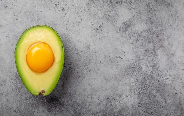 Pokarmy bogate w zdrowe tłuszcze dla zbilansowanego odżywiania: surowe żółtko jajka w świeżo pokrojonym pół awokado na szarym kamiennym tle. dieta ketogeniczna o niskiej zawartości węglowodanów lub koncepcja czystego jedzenia, widok z góry z miejscem na tekst