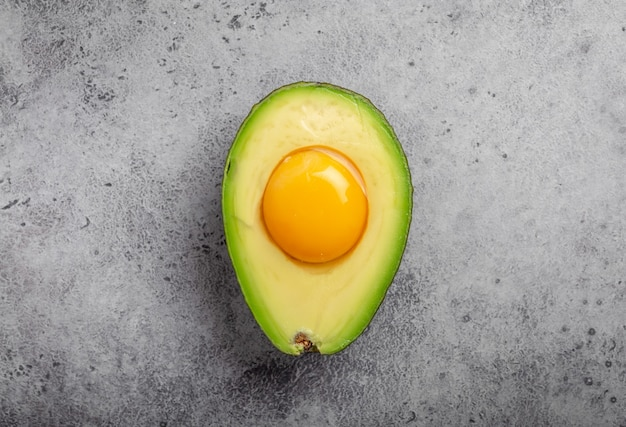 Pokarmy bogate w zdrowe tłuszcze dla zbilansowanego odżywiania: surowe żółtko jajka w świeżo pokrojonym pół awokado na szarym kamiennym tle. dieta ketogeniczna o niskiej zawartości węglowodanów lub koncepcja czystego jedzenia, widok z góry