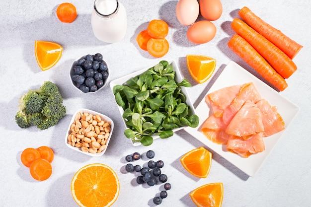 Pokarmy, które pomagają zachować zdrowe oczy, produkty do utrzymania dobrego wzroku. czarna tablica z miejscem na kopię, asortyment żywności dla zdrowia oczu na betonowym tle, płaski układ, widok z góry, nikt