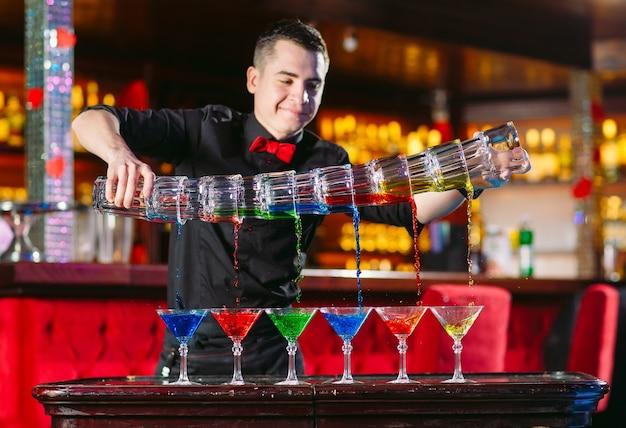 Pokaz barmański. barman nalewa koktajle alkoholowe.