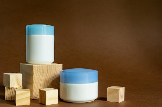 Pokaż drewniane podium z słoikami do kremów na brązowym tle. pojemniki do pielęgnacji twarzy. makieta kosmetyków. produkty na dzień i na noc
