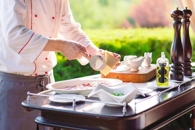 Pokaż kuchnię. kucharz przygotowuje rodzinę carpaccio dla gości restauracji.