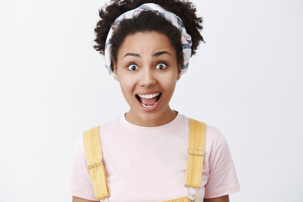 Pokaż mi prawdziwy kolor emocji. portret podekscytowanej, pod wrażeniem i zaskoczonej, przystojnej afroamerykanki w opasce i żółtym kombinezonie, uśmiechnięta z opuszczoną szczęką, podekscytowana szarej ściany