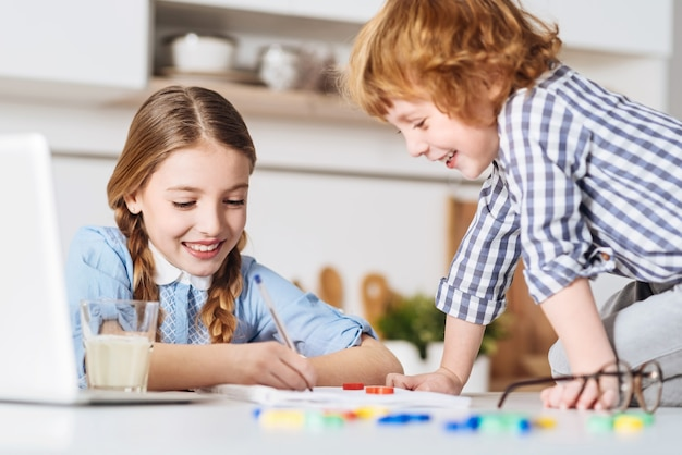 Pokaż mi swoje notatki. zabawny, uroczy rudowłosy chłopiec siedzący tuż przy stole obok swojego rodzeństwa i próbujący sprawić jej przyjemność, spędzając z nią weekend w domu