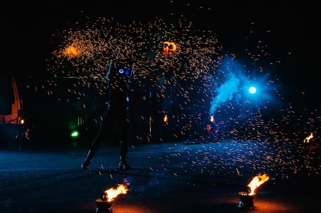 Pokaz ognia, taniec z płomieniem, mistrz żonglerki fajerwerkami, występ na świeżym powietrzu, rysuje ognistą postać w ciemności, jasne iskry w nocy. mężczyzna w garniturze led tańczy z ogniem.
