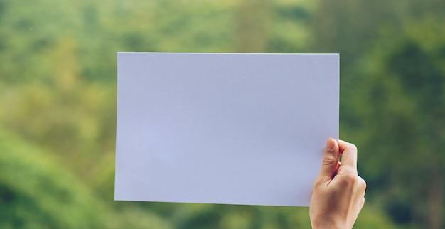 Pokaż papier firmowy w ręku na tle przyrody