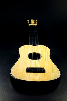 Pokaz ukulele na czarnym tle.