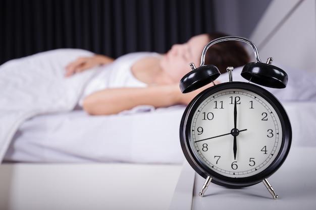 Pokaz zegarowy godzina szósta i kobieta śpiąca na łóżku
