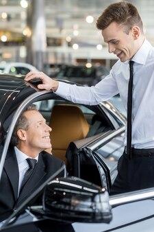 Pokażę ci wszystkie funkcje. pewny siebie dojrzały mężczyzna jonowy strój formalny siedzący na przednim siedzeniu samochodu i rozmawiający ze sprzedawcą samochodów stojącym obok niego