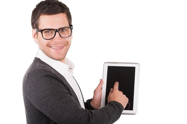Pokażę ci wszystkie funkcje tego gadżetu! wesoły młody człowiek trzyma cyfrowy tablet i wskazuje go, stojąc na białym tle