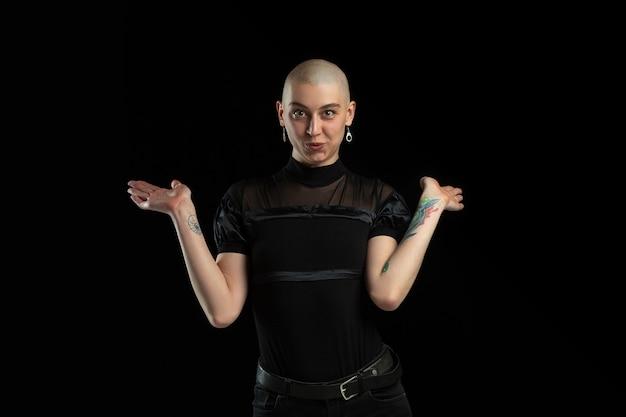 Pokazujące, słodkie. monochromatyczny portret młodej kobiety kaukaski łysy na białym tle na czarnej ścianie.