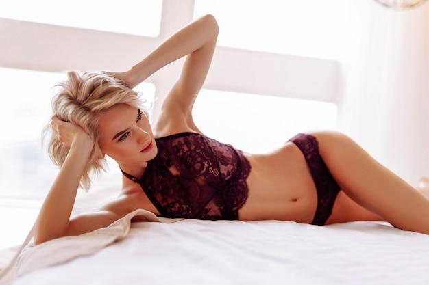 Pokazuje ciało. młoda piękna dziewczyna leżąca na łóżku w bieliźnie pokazująca swoje niesamowite ciało