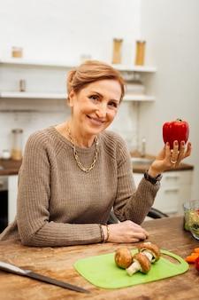 Pokazuje czerwoną paprykę. radosna, atrakcyjna dorosła dama ubrana w beżowy sweter i niosąca czerwoną paprykę podczas gotowania