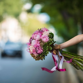 Pokazuje purpurowy bukiet róż i kwiatów nici w widoku ulicy