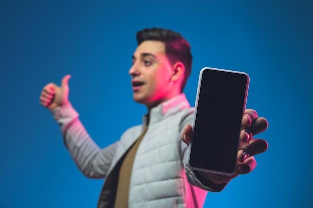 Pokazuje pusty ekran telefonu kaukaski portret mężczyzny na niebieskiej ścianie studia