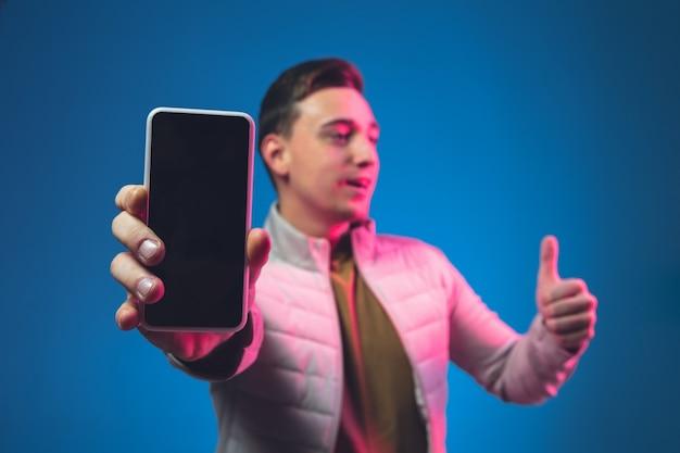 Pokazuje pusty ekran telefonu portret mężczyzny rasy kaukaskiej na niebieskiej ścianie w różowym neonowym świetle.