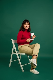 Pokazuje pusty ekran telefonu. portret młodej pięknej kobiety z azji wschodniej na zielonym tle z copyspace.