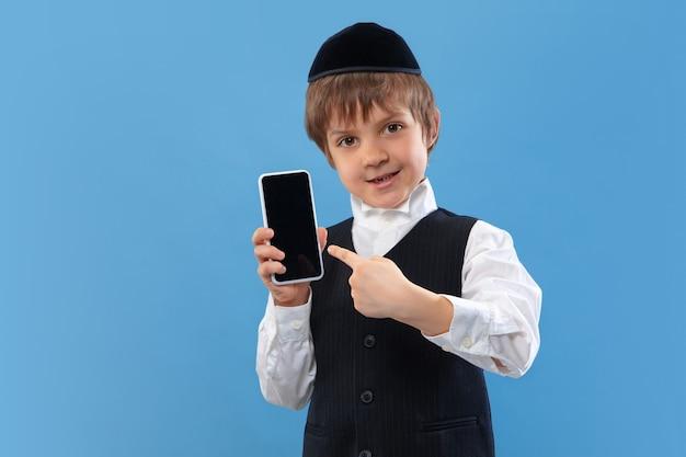 Pokazuje pusty ekran telefonu. portret ortodoksyjnego żydowskiego chłopca na białym tle na ścianie niebieski studio.