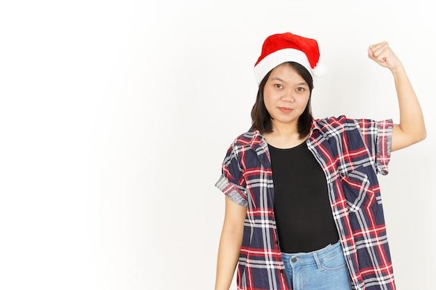 Pokazuje siłę i wznoszące się ramiona pięknej azjatki ubranej w czerwoną koszulę w kratę i santa hat