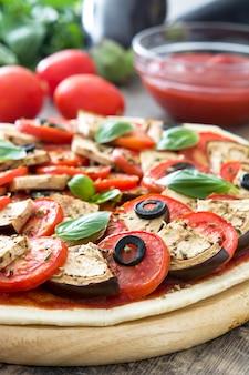 Pokazuje wegetariańską pizzę z bakłażanem, pomidorem, czarnymi oliwkami, oregano i bazylią na drewnianym stole
