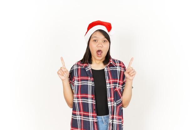 Pokazywanie i wskazywanie produktu pięknej azjatki ubranej w czerwoną koszulę w kratę i santa hat