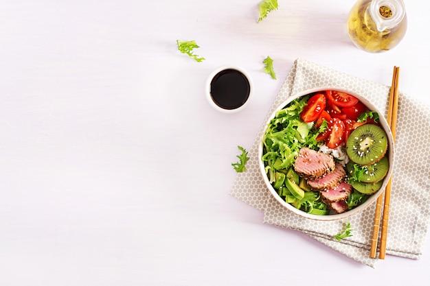 Poke bowl. miska buddy. tradycyjna sałatka z kawałkami średnio rzadkiego grillowanego tuńczyka ahi i sezamu z sałatką ze świeżych warzyw i ryżem na talerzu