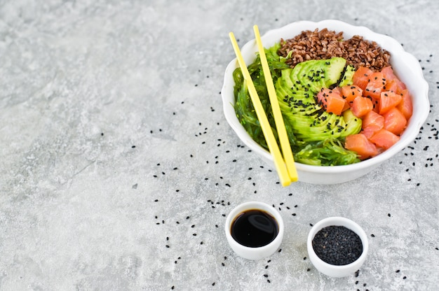 Poke bowl. składniki: łosoś, awokado, brązowy ryż, algi.