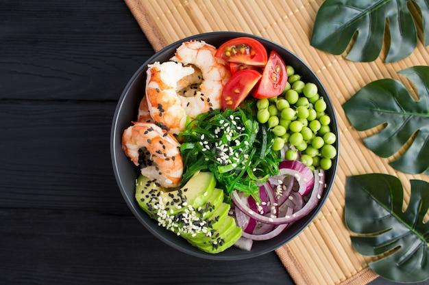 Poke bowl z czerwonymi krewetkami i warzywami w ciemnej misce na tropikalnym tle. widok z góry. zbliżenie. miejsce.