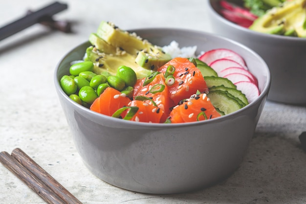 Poke bowl z łososiem, ryżem, awokado, fasolą edamame, ogórkiem i rzodkiewką w szarej misce. hawajska miska ahi poke, szare tło.