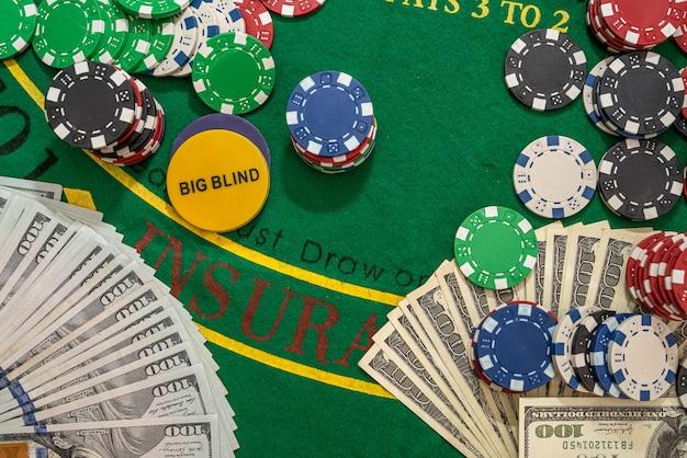 Poker żetony z karty i banknotów dolara na zielonym stole w kasynie. hazard online. teksas