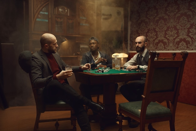 Pokerzyści z kartami i żetonami w kasynie. uzależnienie, dom hazardowy