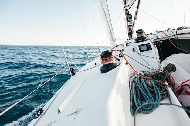 Pokład profesjonalnej żaglówki lub jachtu regatowego podczas zawodów w słoneczny i wietrzny letni dzień, szybko poruszający się przez fale i wodę, ze spinakerem w górę