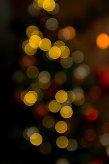 Pokój bożonarodzeniowy z choinką i świątecznym oświetleniem bokeh
