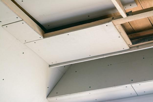 Pokój budowlany z płytami gipsowo-kartonowymi. wykonywanie podwieszanego sufitu za pomocą drewnianej ramy i suchej zabudowy w prywatnym domu