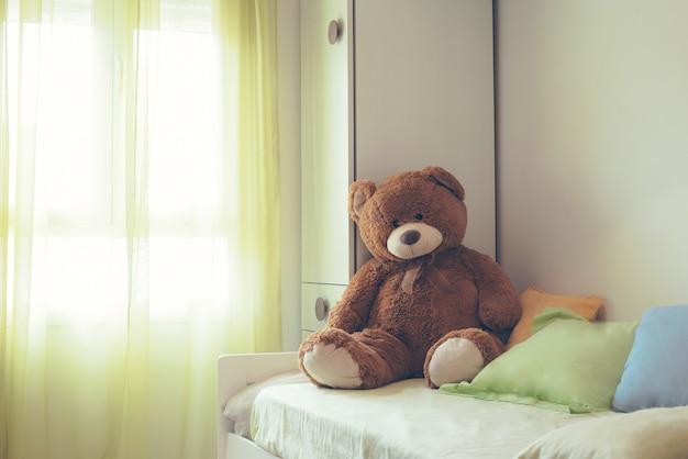 Pokój childrem z brązowym misiem na łóżku