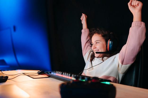 Pokój do nauki małego gracza świętującego zwycięstwo na krześle do komputera do gier, klawiatury w niebieskim neonowym kolorze i czarnym tle.