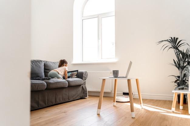 Pokój dzienny z dzieckiem oglądającym bajki na kanapie i domowym gabinecie rodzica