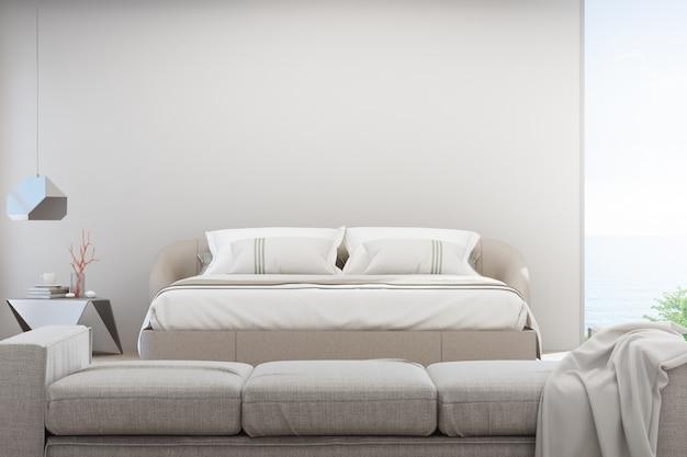 Pokój dzienny z widokiem na morze i sypialnia luksusowego letniego domu na plaży z sofą w pobliżu podwójnego łóżka.